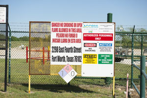 Signs posted on gates of fracking pad near Fort Worth Texas.